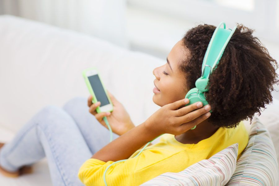Mulher ouvindo música no fone de ouvido com o intuito de melhorar sua saúde emocional