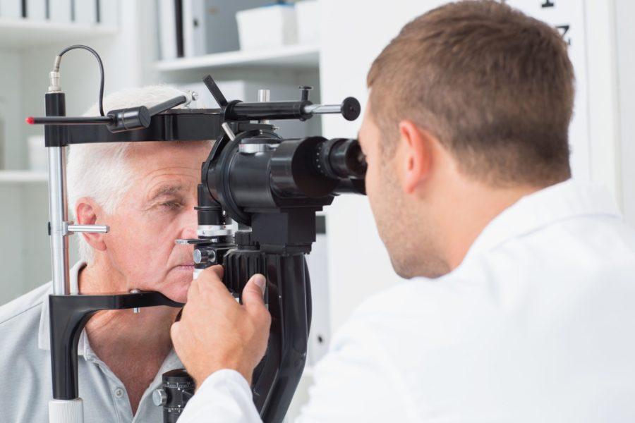 Oftalmologista examinando um senhor para ver se ele precisa de fazer a cirurgia de catarata