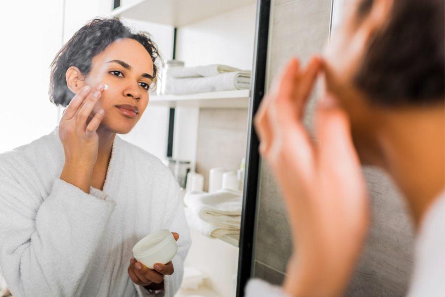 Mulher negra de roupão em frente ao espelho passando creme no rosto antes de dormir como um dos cuidados noturnos com a pele