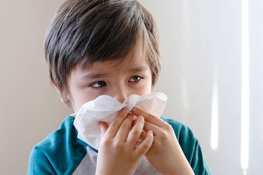 Menino com gripe assoando o nariz com papel higiênico