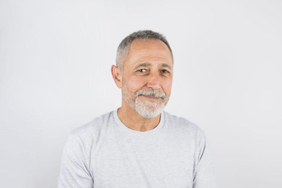 Homem de meia idade sob um fundo cinza representando a glaucoma