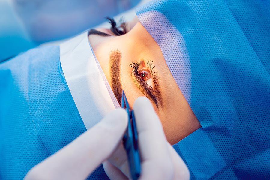Close de rosto de mulher com proteção para cirurgia de colocação de lente intraocular. Mão de oftalmologista aproxima uma pinça da única parte à mostra do rosto dela que é a região dos olhos.
