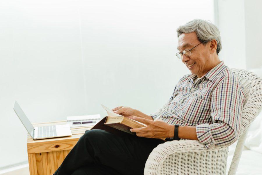 Homem idoso feliz lendo um livro para controlar a ansiedade e o estresse na quarentena