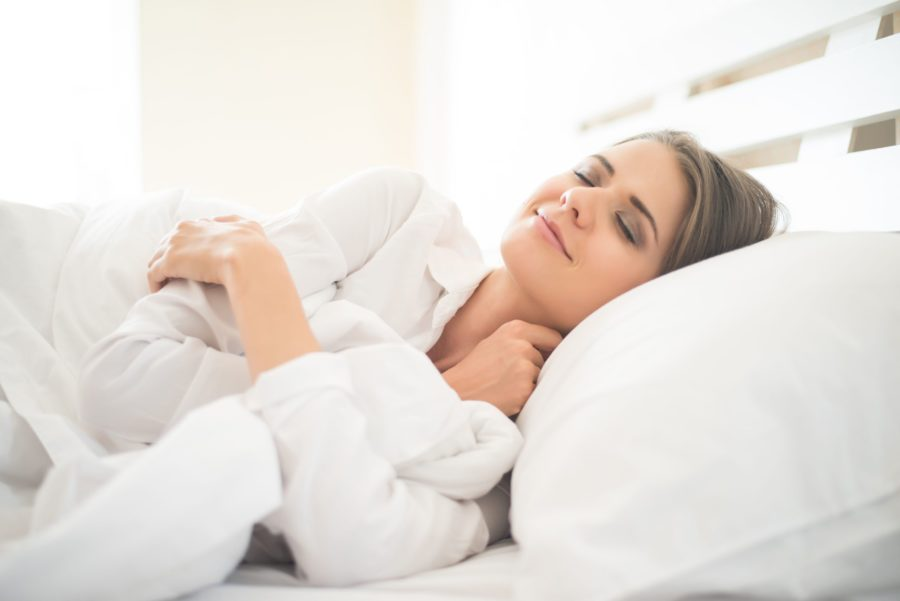 Mulher com semblante tranquilo dormindo bem em sua cama