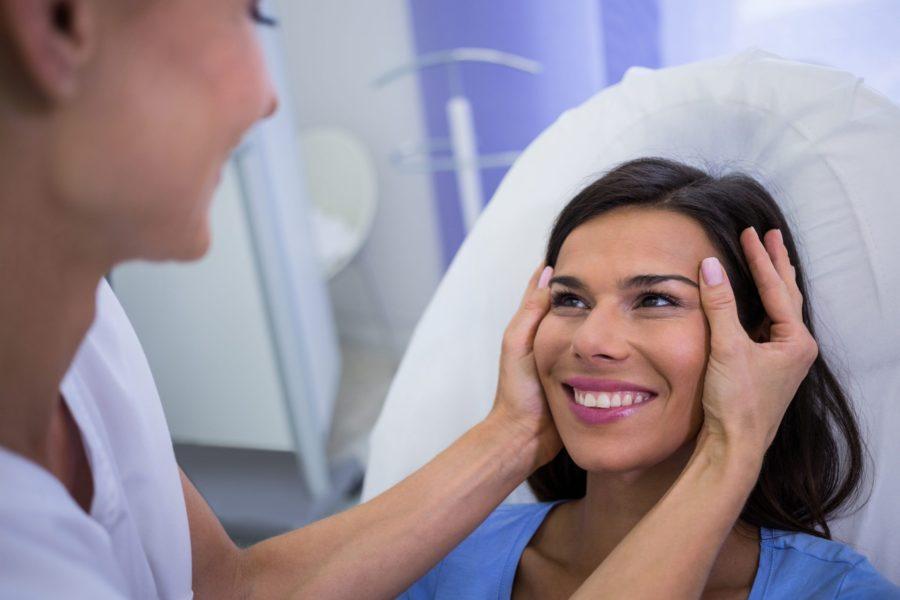 Mulher sorridente tendo a pele do rosto esticada por dermatologista para saber se precisa da elevação dos supercílios