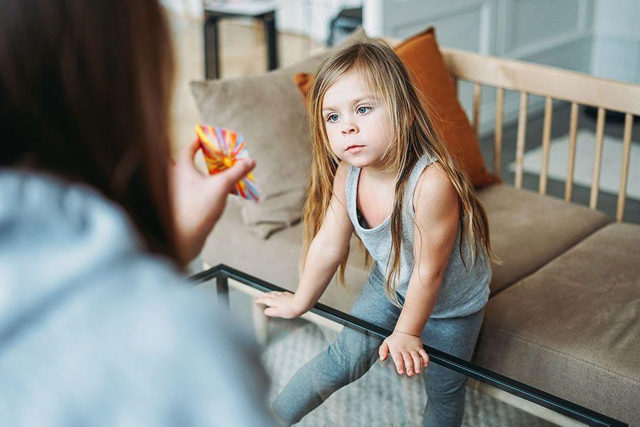 Menina com autismo apoiado em uma mesa olhando fixamente para uma carta que um mulher está mostrando