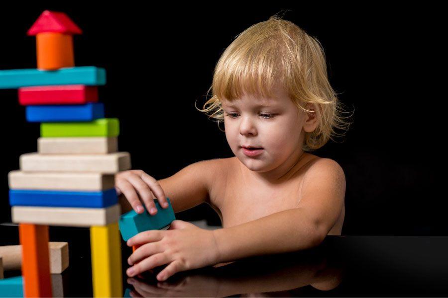 Menino com autismo brincando sozinho com brinquedos coloridos de montar