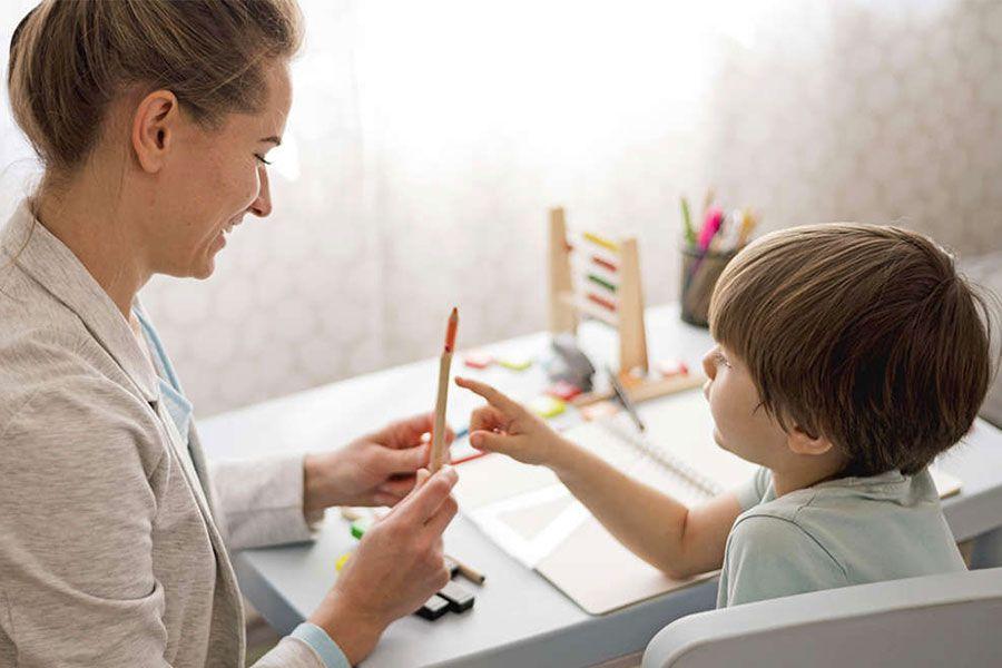 Educadora fazendo exercícios com uma criança autista envolvendo lápis