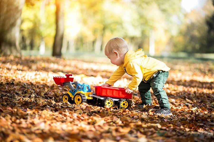 Criança autista brincando em um parque ao ar livre com uma escavadeira e um caminhão de brinquedos. Ela está vestindo roupas de frio e pisando em um chão cheio de folhas.