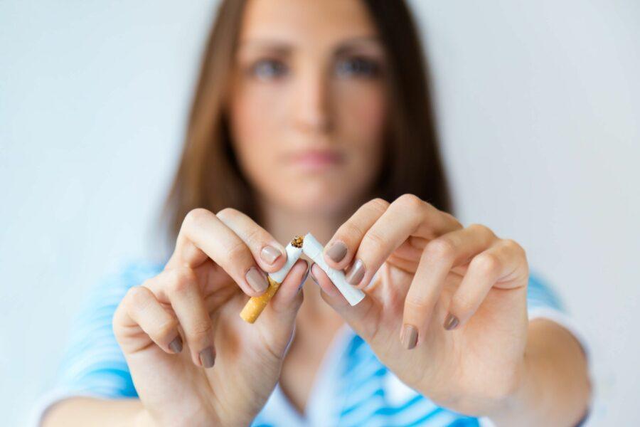 Mulher quebrando um cigarro ao meio indicando que está parando de fumar