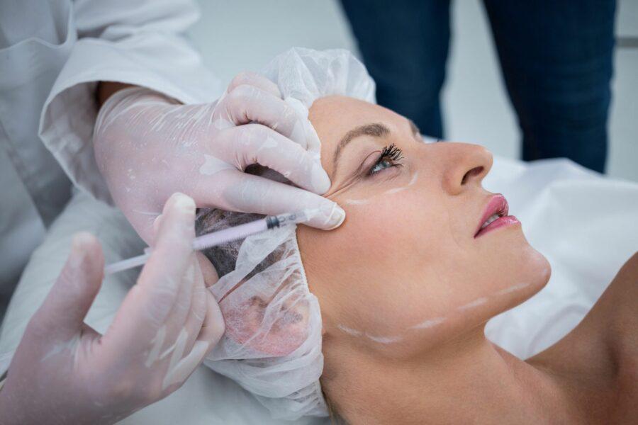 Mulher recebendo uma injeção de preenchimento dérmico na região dos olhos para se livra dos pés de galinha