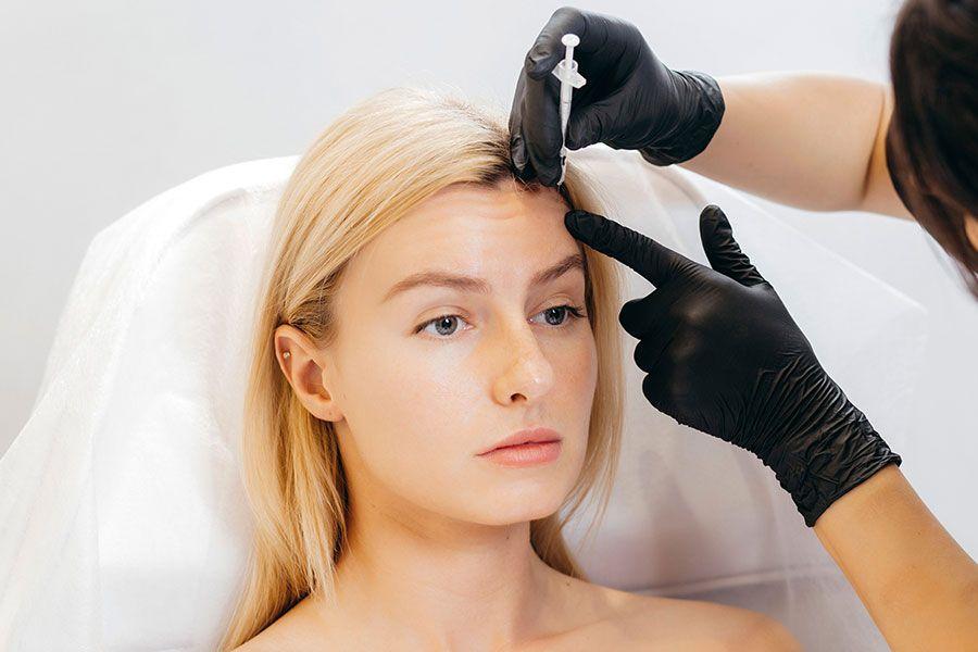 Mulher com rugas na testa tendo uma injeção de botox aplicada na testa