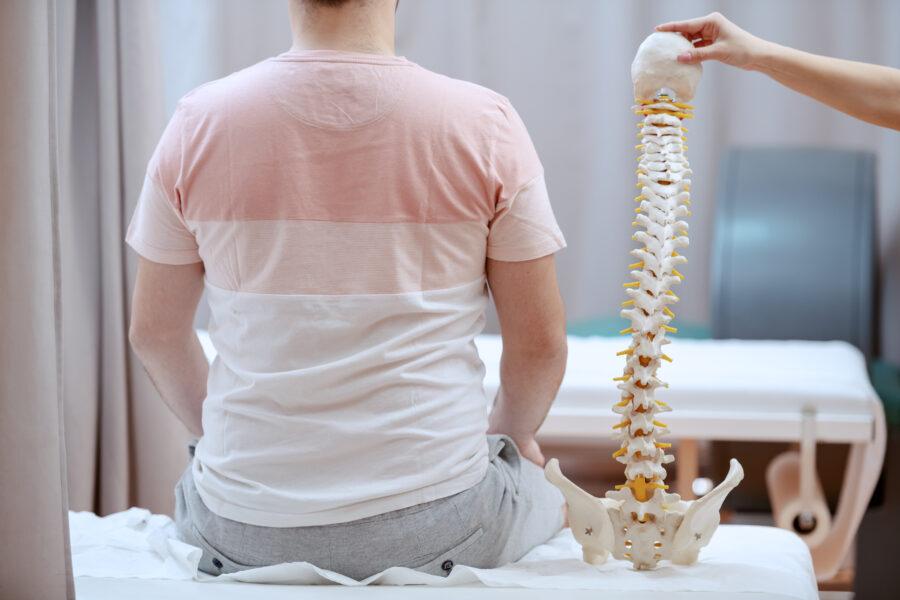 Paciente de costas sentado na cama do consultório e um médico segurando um modelo de uma coluna vertebral com escoliose