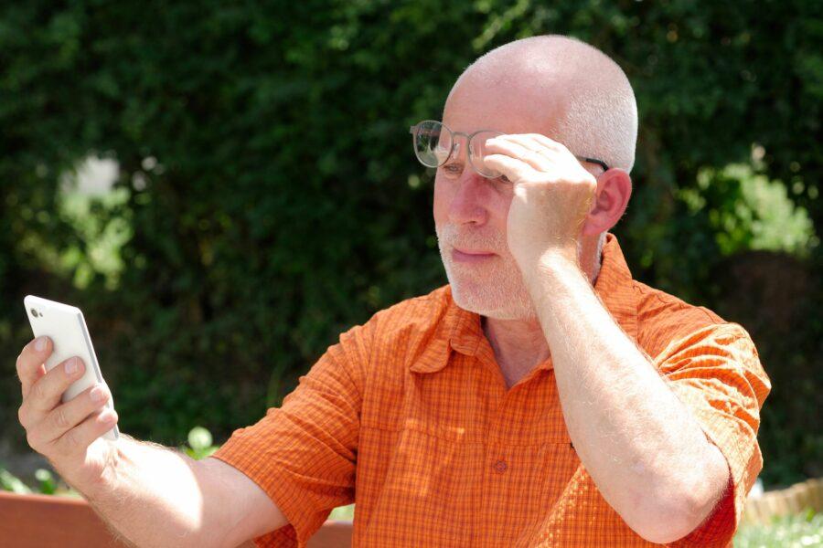 Homem mais velho levantando os óculos e esticando o braço para afastar o celular. Ele está com dificuldade para ler o que está na tela por causa da vista cansada