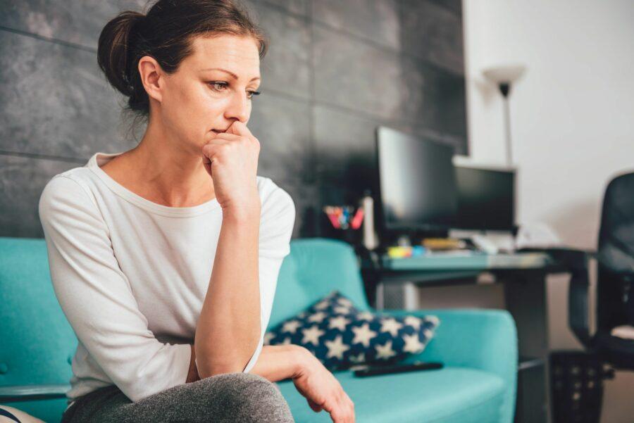 Mulher com ansiedade e depressão sentada no sofá. Ela está com olheiras e a mão apoiada na boca.