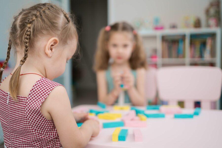 Menina com autismo brincando com brinquedos em cima de uma mesa