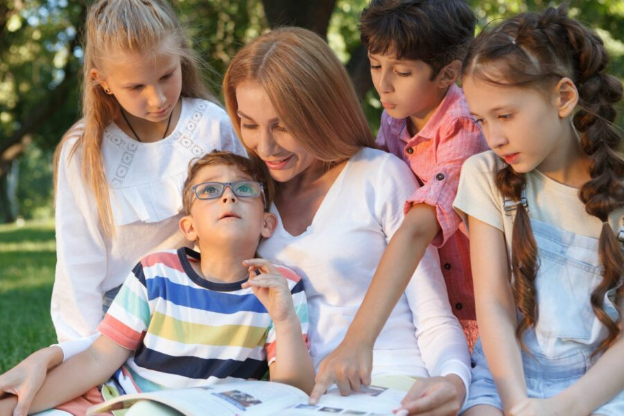 Mãe e seus filhos sentados na grama de um parque. Um dos filhos tem autismo e está no centro cercado pelos demais integrantes da família.