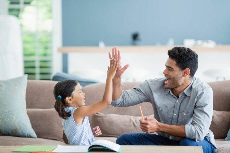 Pai fazendo toca aqui com a filha, enquanto a ajuda com o dever de casa usando educação positiva. Eles estão na sala de casa e na mesa tem material de estudos.