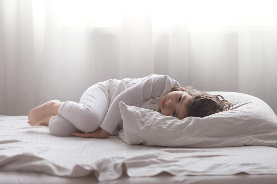 Menina autista que possui distúrbios do sono deitada na cama tentando dormir