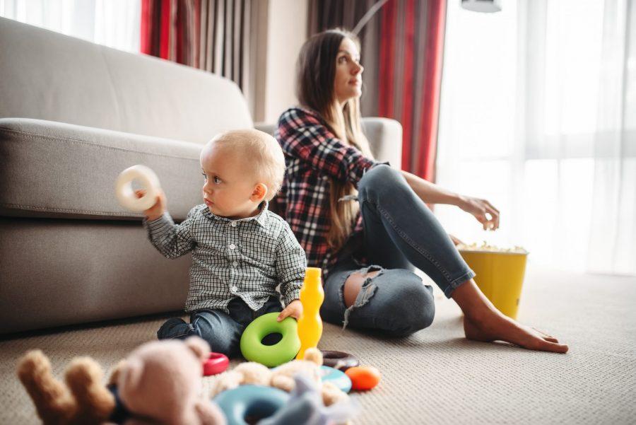 Criança com autismo brincando no chão com brinquedos coloridos no primeiro plano enquanto, ao fundo, a mãe, também no chão, apoiada no sofá assiste filme e come pipoca para preservar sua saúde mental.