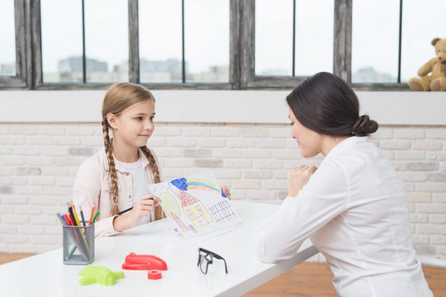 Menina com autismo mostrando um desenho para sua terapeuta ocupacional