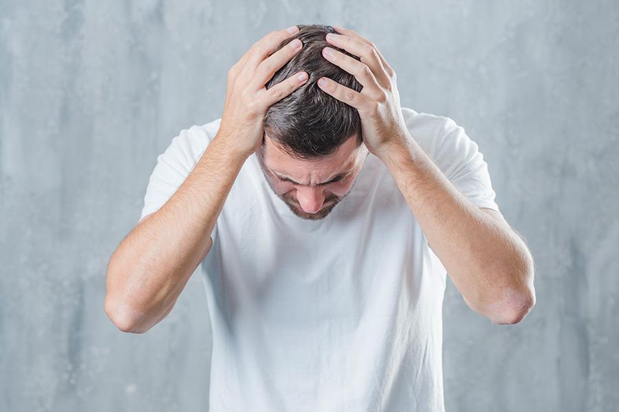 Homem com síndrome do pânico com as mãos na cabeça demostrando estar desesperado