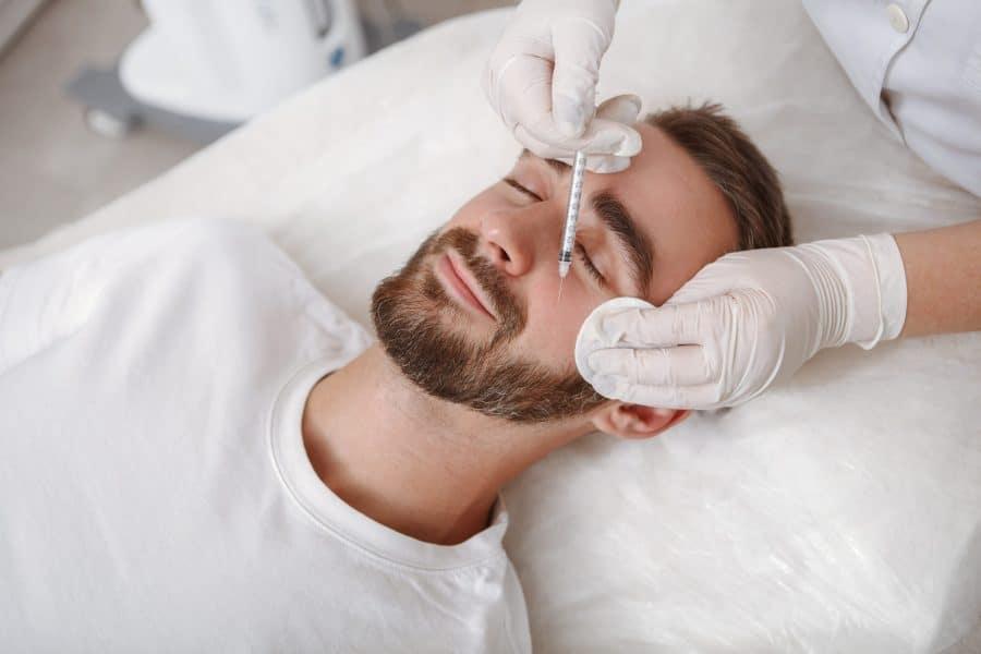 Dermatologista aplicando uma injeção no rosto de um homem. Isso é parte do procedimento de harmonização facial masculina.