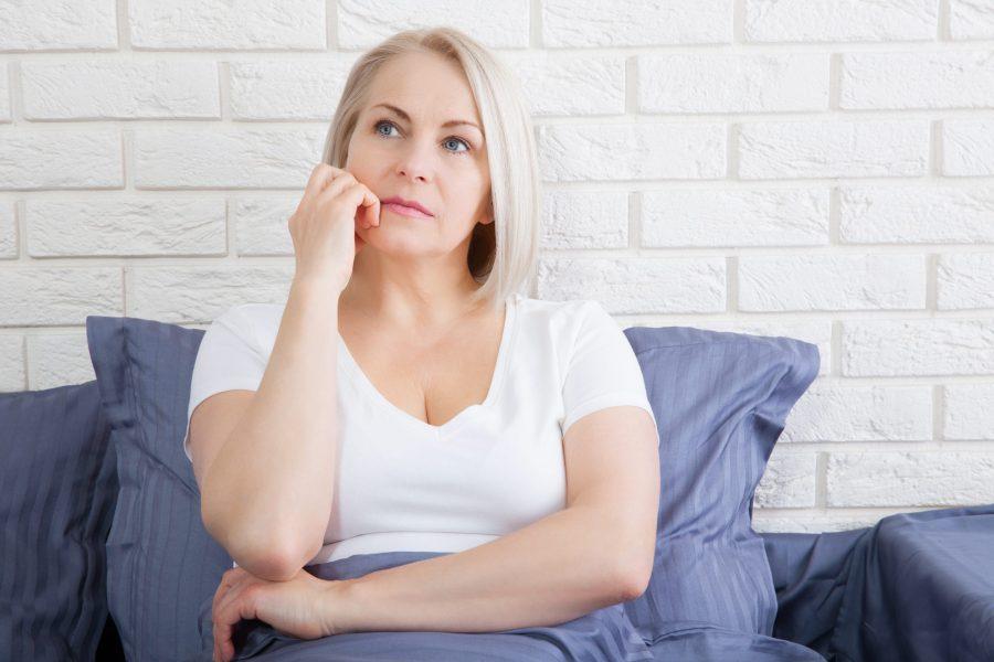 Mulher de meia idade que está na menopausa sentada na cama com a mão no rosto e expressão pensativa.