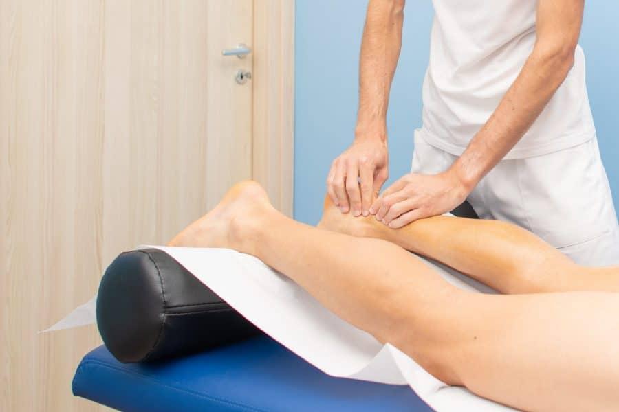 Em uma clínica de fisioterapia, uma pessoa em uma maca tem o tendão de aquiles massageado por um fisioterapeuta por estar com tendinite do calcâneo.