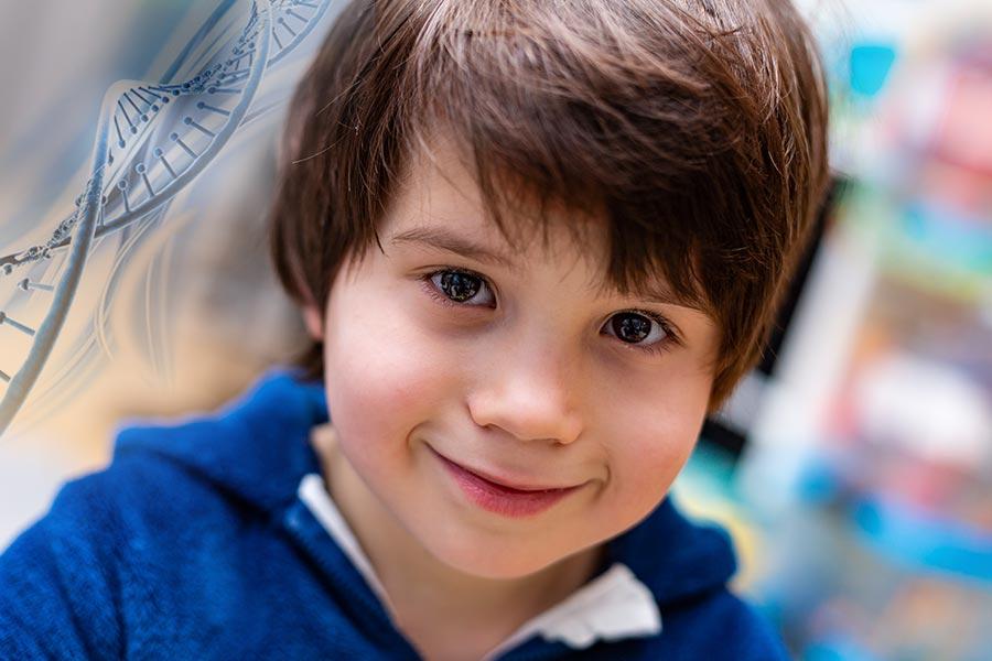 Retrato de menino com autismo. Na esquerda tem um DNA para representar a genética.
