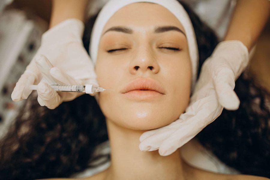 Mulher no dermatologista recebendo um injeção de ácido hialurônico