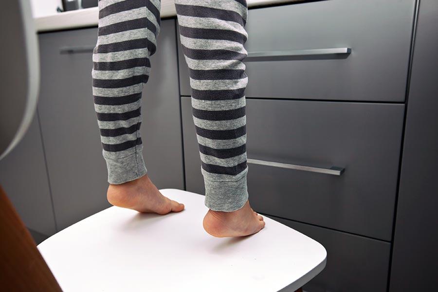 Criança com autismo tentando pegar algum objeto que está na bancada da cozinha. Ela está na ponta dos pés em uma cadeira. Representação do risco de acidentes no TEA.