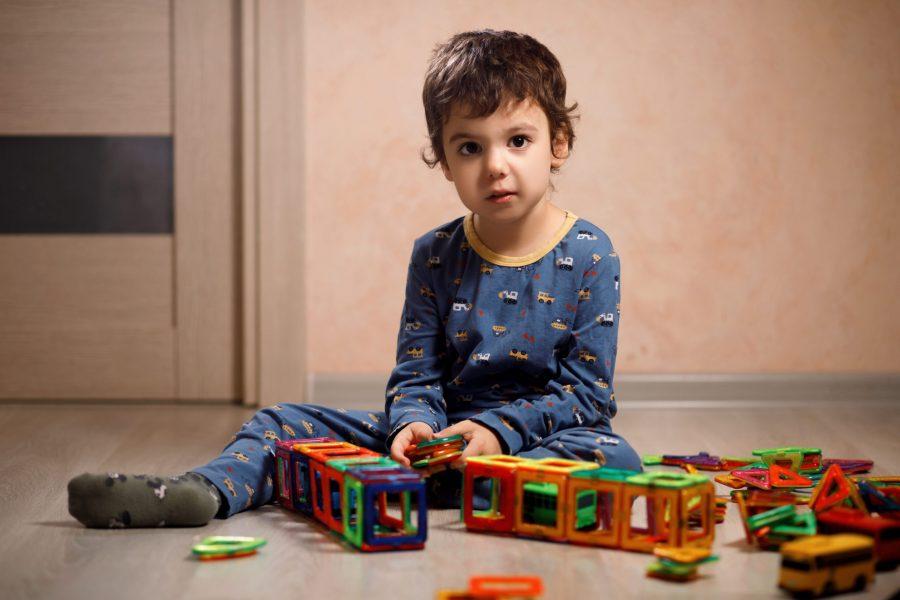 Menino com autismo usando pijama e brincando no chão com blocos de montar.