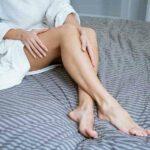 Mulher de roupão na cama passando as mãos nas pernas depiladas. Ela usou o melhor método de depilação para o caso dela.