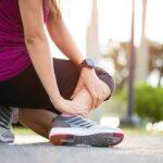 Mulher ajoelhada no chão com as mãos no tornozelo indicando entorse de tornozelo. Ela estava praticando corrida.