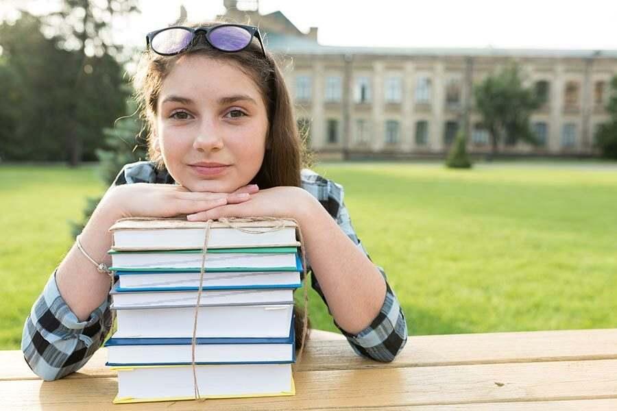 Menina ao ar livre apoiando o queixo em um pilha de livro. Ela está com óculos descansando na cabeça e ao fundo um prédio antigo. Ela tem exotropia intermitente.